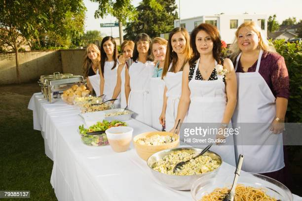 Group of Hispanic women behind buffet table