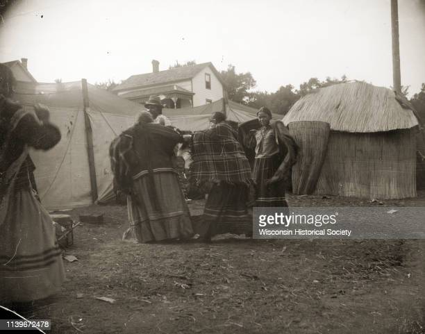 A group of HoChunk women wrapped in shawls gathering at the temporary HoChunk village Black River Falls Wisconsin 1908 Identified as the Homecoming...