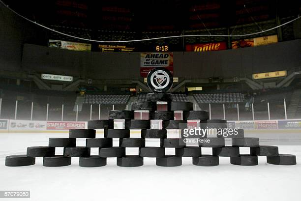 A group of hockey pucks is arranged on the ice in a pyramid which is topped by one bearing the logo fo the Vancouver Giants before a regular season...