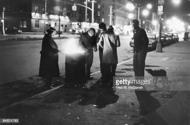 A group of homeless men stand around a fire in an oil drum on the Bowery New York New York January 8 1972