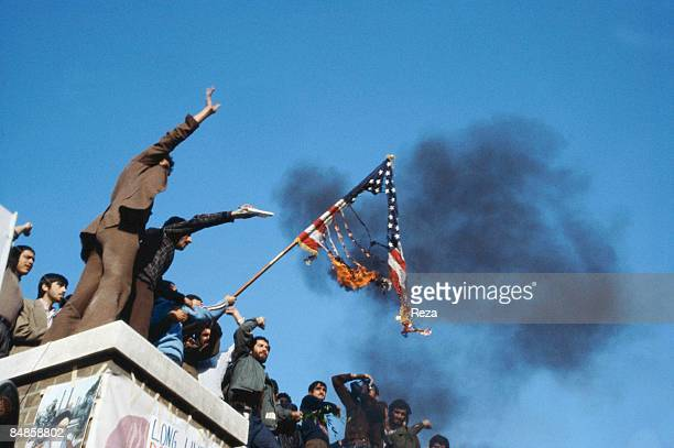A group of hostage holders putting fire on the Amercian flag on the roof of the occupied US embassy during the US hostage crisis which was a...
