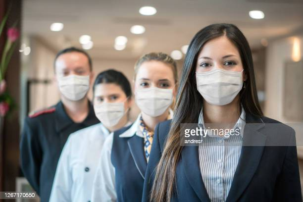 group of hotel workers wearing facemask - hotel stock pictures, royalty-free photos & images