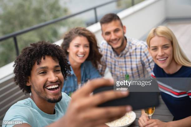 Group of house mates outdoors at home taking a selfie