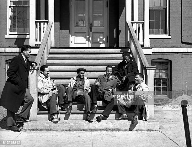 A group of Howard University students relax on the stoop of a building Washington DC Winter 1942