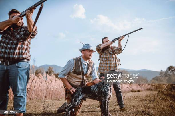 group of hunters with their dogs in action - anatra uccello acquatico foto e immagini stock