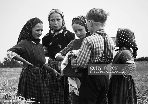 A group of Hutterite children standing in a field on the colony Northeast Alberta Canada 1963 Photo taken during the National Film Board of Canada's...