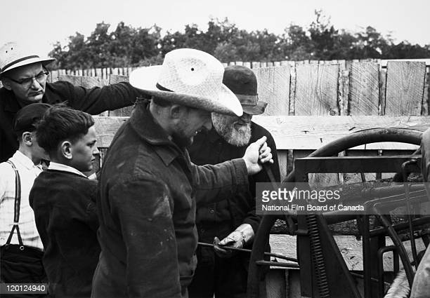 A group of Hutterite farmers are inspecting some agricultural machinery Northeast Alberta Canada 1963 Photo taken during the National Film Board of...