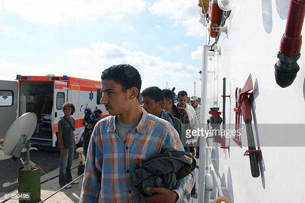 Group of illegal immigrants are escorted by Italian police onto a military plane bound for Libya from Lampedusa's airport, 04 October 2004. Italy on...