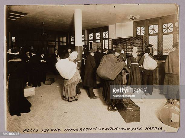 Group of immigrants collect their belongings as they pass through the Ellis Island Immigration Station on their way to other destinations in the U.S....