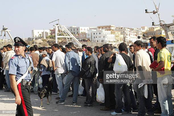 A group of Immigrants escorted by carabinieri wait on Lampedusa island harbor docks before embarking on a ferryboat to Porto Empedocle in Sicily 08...