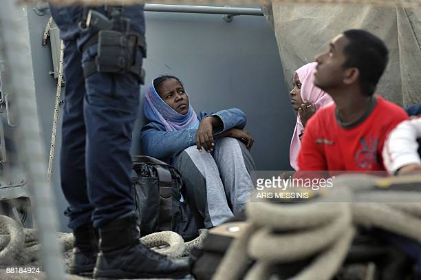 A group of immigrants sits on May 25 2009 on the deck of a Greek Coast Guard ship in the port of the small Greek Aegean Sea island of Agathonissi...