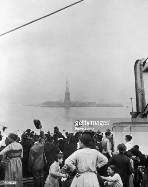 Group of immigrants traveling aboard a ship celebrate as they catch their first glimpse of the Statue of Liberty and Ellis Island in New York Harbor.