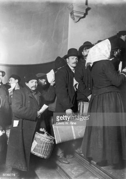Group of immigrants walk up the stairs to the entrance terminal at Ellis Island, carrying their luggage, New York City. Several men look back at the...