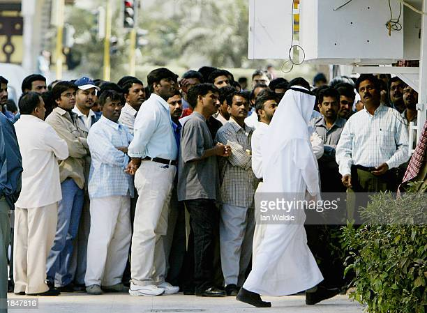 Group of Indian ex-patriots gathers on the street to watch the World Cup cricket match between India and New Zealand as a local Arab walks by March...
