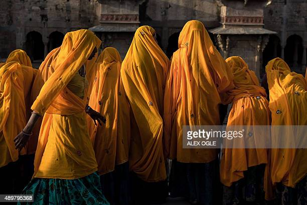 Group of Indian Hindu women watch youths play in the water at the bottom of the historic Chand Baori stepwell in Abhaneri village of western...