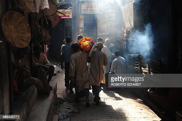 A group of Indian men carry the body of a deceased person through the narrow streets of Varanasi on May 11 as they head to the banks of the River...