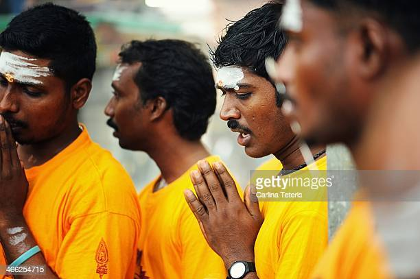 Group of Indian men pray before receiving piercings through their tongues during Taipusam festival, honouring the Hindu God, Murugan in Singapore