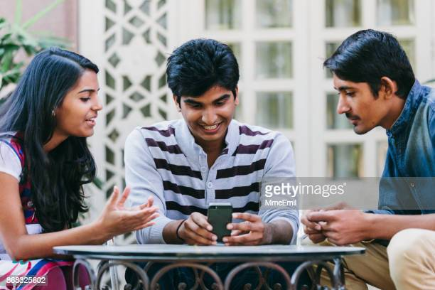 group of indian millennials looking at a smartphone around a table on a patio. - stereotypically middle class stock photos and pictures