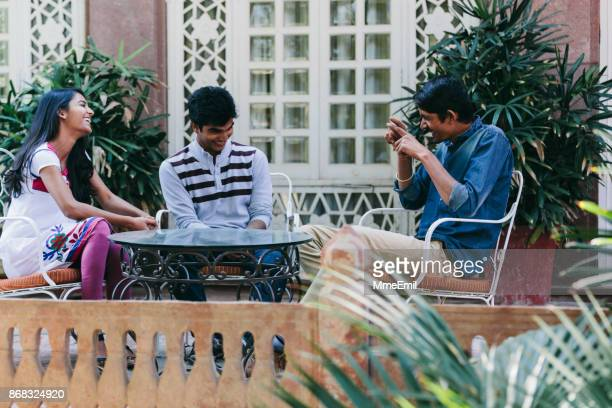group of indian millennials talking about life around a table on a patio. - storyteller stock pictures, royalty-free photos & images