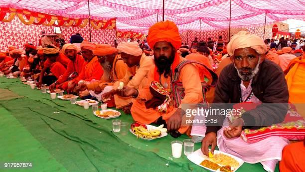 食品を一緒に食べるインド サードゥのグループ - カースト ストックフォトと画像