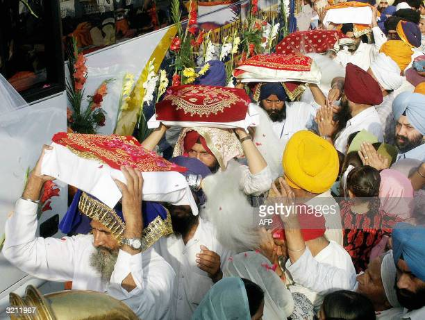 A group of Indian Sikhs carry the Sikh holy book the Guru Granth Sahib towards a waiting bus in Amritsar 03 April 2004 which will transport them to...
