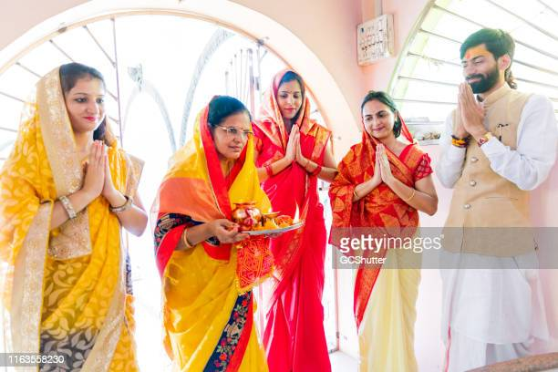 group of indian women and a priest performing prayers at a hindu temple - hinduism stock pictures, royalty-free photos & images