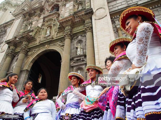 Group of indigenous girls wearing typical costumes standing up in front of the cathedral when hundreds of Quechuaspeaking Indigenous people devotees...