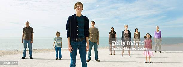 Group of individuals standing on beach, smiling optimistically