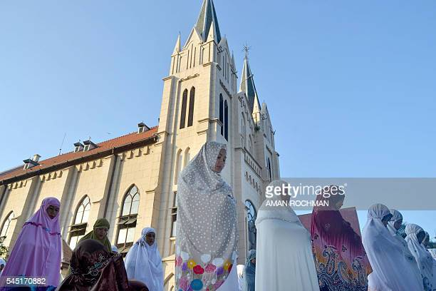 A group of Indonesian Muslims offers morning prayers to mark Eid alFitr on the grounds of the Hati Kudus Jesus church in Malang East Java on July 6...