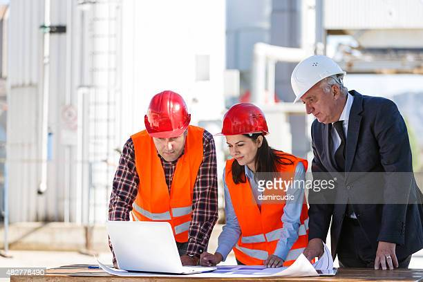 group of industrial engineers with computer outdoor - gas refinery stock photos and pictures