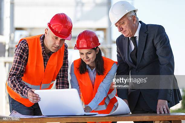 Group of industrial engineers with computer outdoor