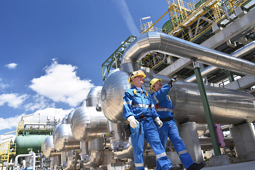 group of industrial workers in a refinery - oil processing equipment and machinery 1039705312