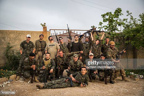 Group of international foreign fighters pose for a photo on April 16 in the outskirts of the north-western Syrian town of Tal Tamr, north of Hasakeh,...