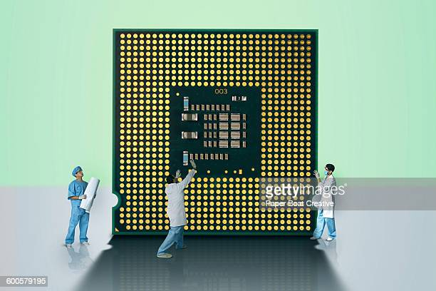 group of inventors holding up a giant microchip