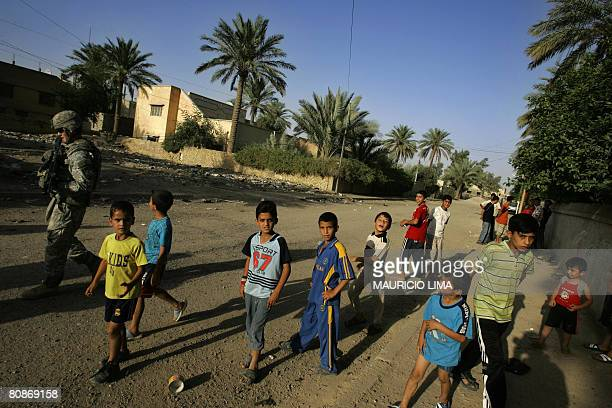 A group of Iraqi boys follow a US soldier of 65th Military Police Company Airborne in a residential Shiite neighborhood in Mahmudiyah some 30...