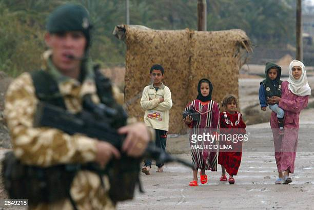 A group of Iraqi children walk past a British soldier from the 1st Battalion of the Light Infantry Division during a patrol in the outskirts of...