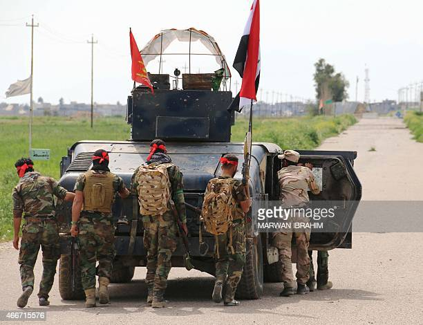 Group of Iraqi fighters made up of Popular Mobilisation units and Shiite Turkmen combatants walk behind a tank as they head towards the city of...