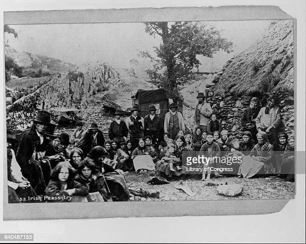 A group of Irish peasants standing outside a house Ireland ca 1880