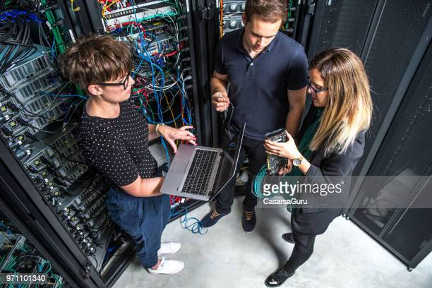 group of it technicians working in server room - computer repair stock pictures, royalty-free photos & images