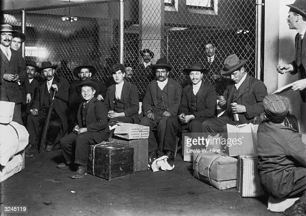 A group of Italian immigrants sit with their cases in a railroad waiting hall on Ellis Island New York