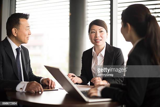 Group of Japanese business people using laptop in meeting