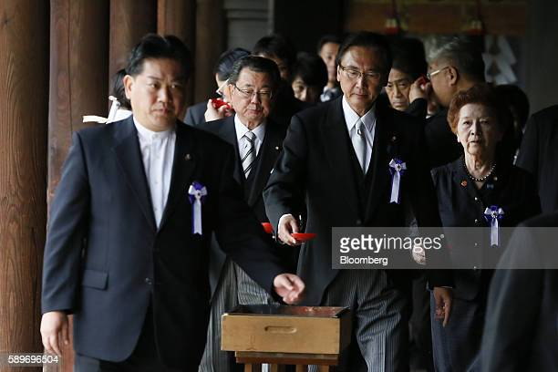 A group of Japanese lawmakers walk down a hallway after offering prayers at the Yasukuni Shrine on the anniversary of Japan's World War II surrender...