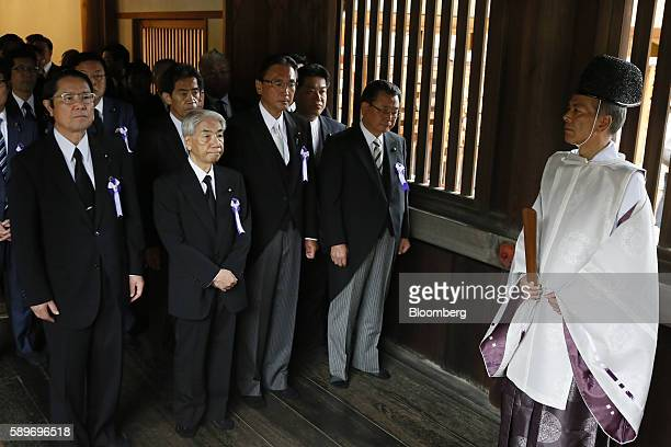 A group of Japanese lawmakers walk down a hallway to offer prayers at the Yasukuni Shrine on the anniversary of Japan's World War II surrender in...