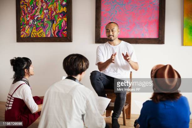 group of japanese men and women sitting in art gallery, holding a discussion. - クリエイティブな職業 ストックフォトと画像