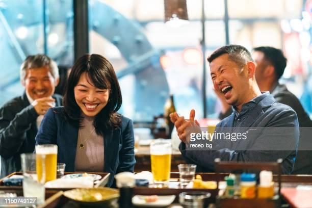 居酒屋日本居酒屋でお祝いのトーストを食べる日本人グループ - 仕事後 ストックフォトと画像