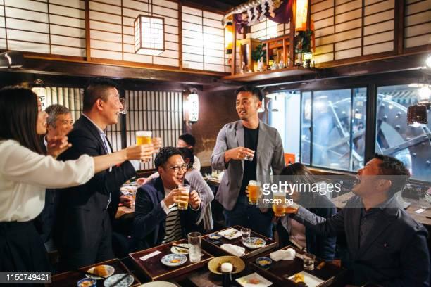 居酒屋日本居酒屋でお祝いのトーストを食べる日本人グループ - 乾杯 ストックフォトと画像