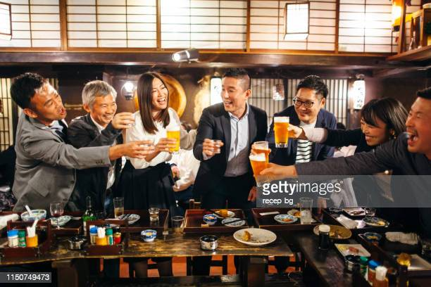 group of japanese people having celebratory toast in izakaya japanese style pub - honour stock pictures, royalty-free photos & images