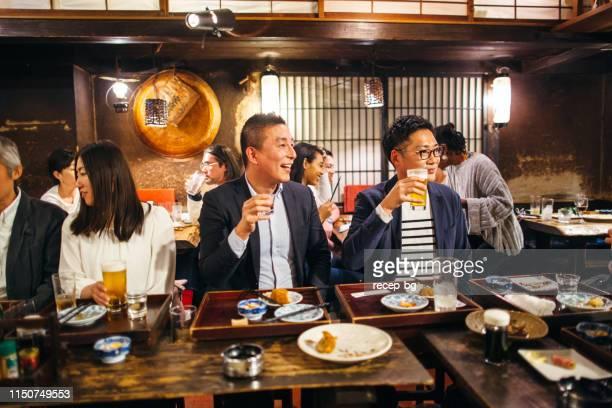 Group of Japanese people talking in Izakaya Japanese style pub