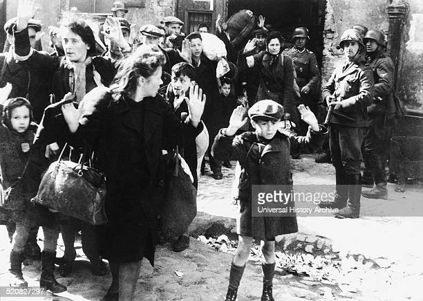 Group of Jewish civilians being held at gunpoint by German SS troops after being forced out of a bunker where they were sheltering during the Warsaw...