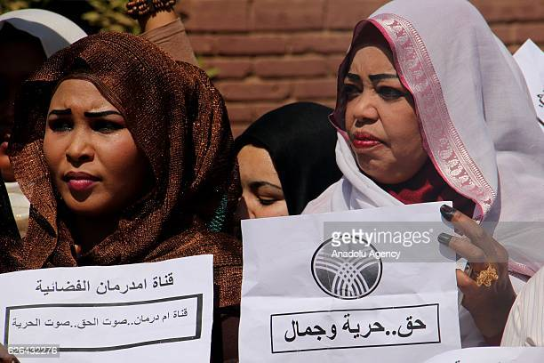 A group of journalists hold banners as they stage a protest against the shut down of the tv channel Omdurman in front of the channel's building in...
